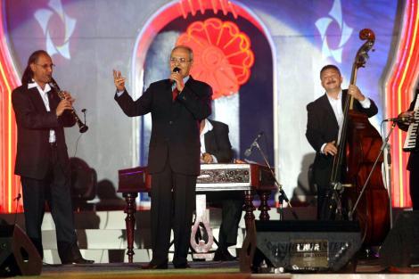 Nelu Ploieșteanu într-un costum negru, pe scenă, cântă la microfon