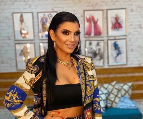 Andreea Tonciu într-un top negru și cu o bluză colorată