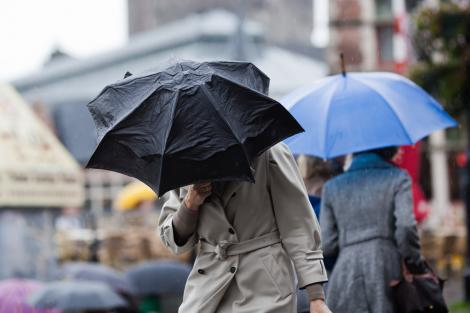 Două persoane cu umbrele care sunt luate de vânt