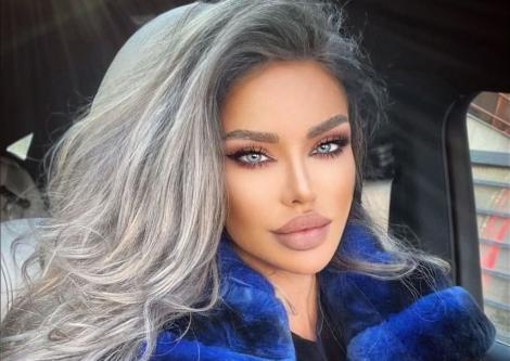 Bianca Drăgușanu cu părul pe o parte și poartă o haină de blană albastră