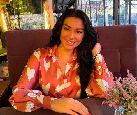Elena Ionescu într-o cămașă roz cu inimioare, ține mână în păr și zâmbește