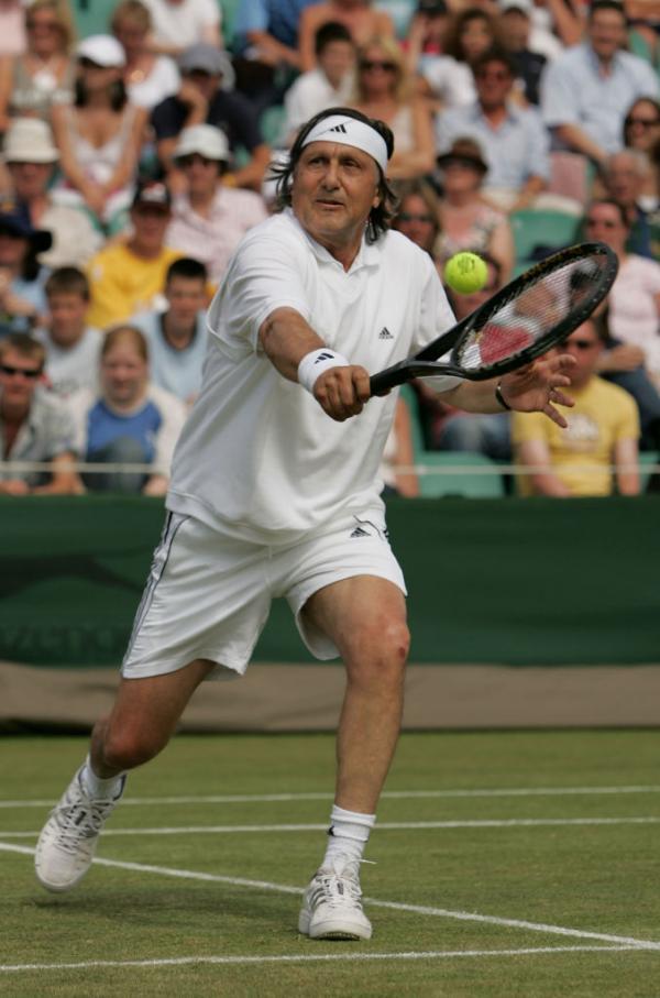 Ilie Năstase, jucând tenis, îmbrăcat în alb