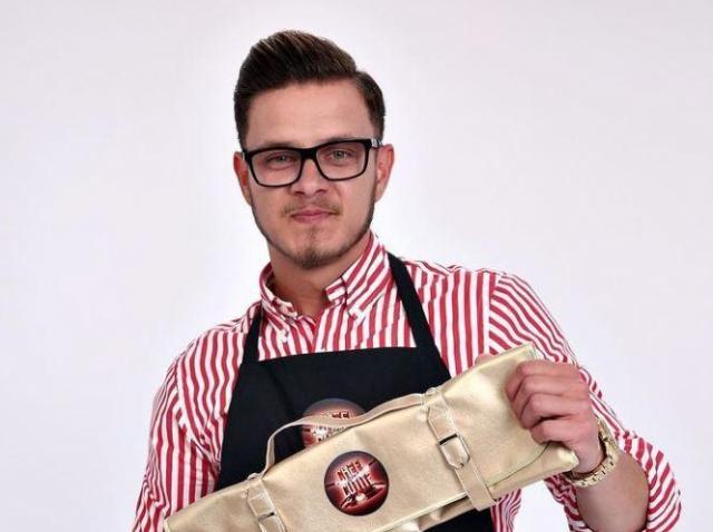 Ionuț Belei într-o cămașă roșie cu dungi albe, ține cuțitul de aur în mână și poartă ochelari