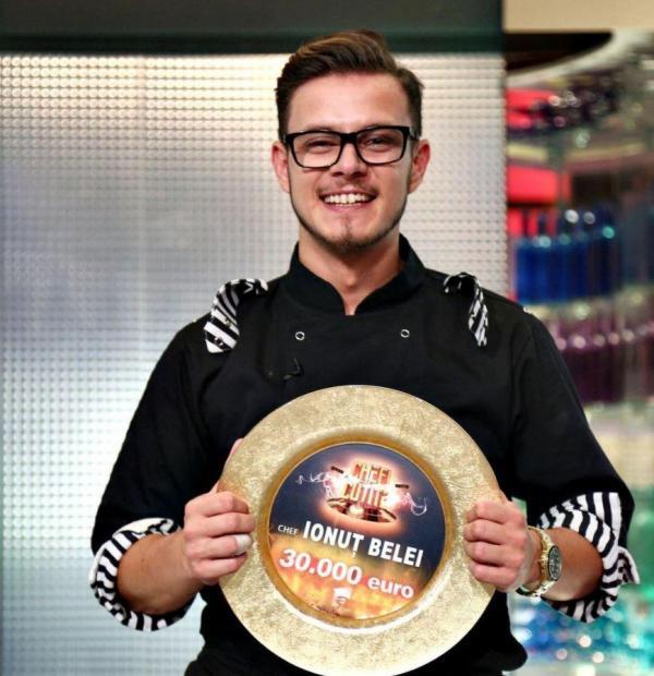 Ionut Belei cu trofeul in mana, imbracat in tunica neagra si poarta ochelari