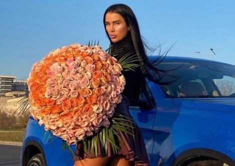 Daniela Crudu într-o fustă mini și o bluză neagră, în mână ține un buchet de trandafiri, iar lângă ea se află o mașină albastră