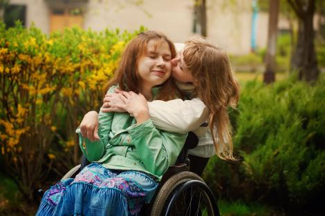 fata in scaun cu rotile, mama sa o saruta pe obraz