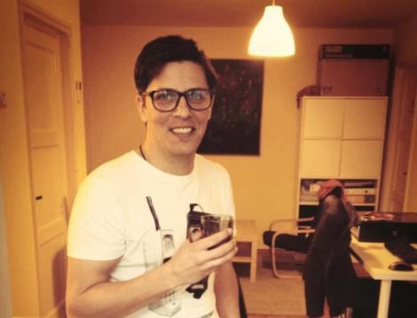 Lucian Viziru într-un tricou alb și poartă ochelari, iar în mână ține o cană