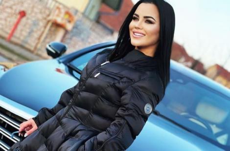 Carmen de la Sălciua intr-o  geacă lungă, neagră și zâmbește, iar în spate are o mașină
