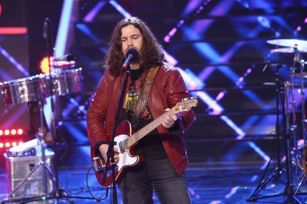 Radu Almășan într-o geacă roșie, cântă la chitară
