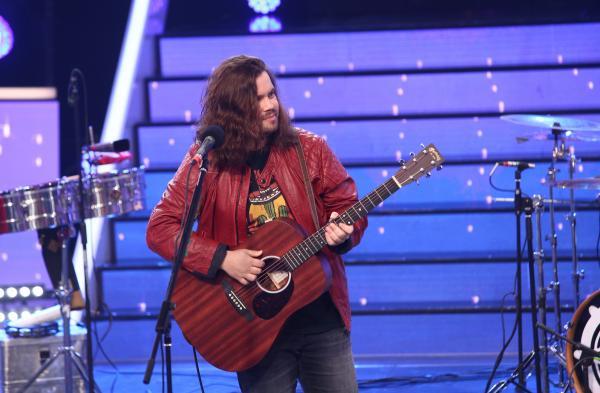 Radu Almășan într-o geacă roșie, pe scena Te cunosc de undeva