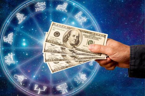 imagine ilustrativă cu discul celor 12 zodii și mâna unei persoane ce ține un teanc de bani