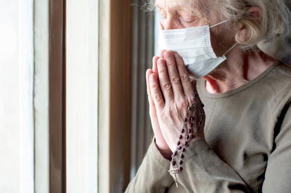femeie care se roaga cu o masca pe fata