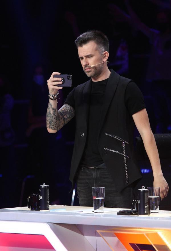 Florin Ristei îmbrăcat în negru și ține un telefon în mână