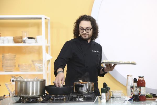 Florin Dumitrescu într-o tunică neagră și gătește