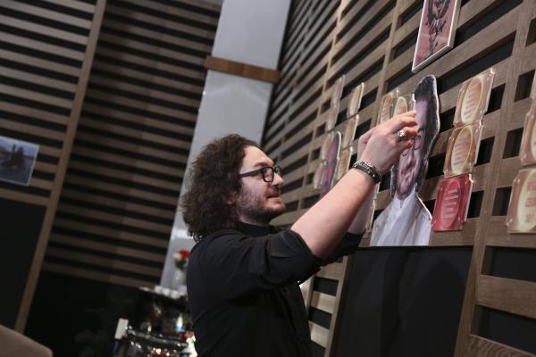 Florin Dumitrescu într-o tunică neagră, lipește amuleta pe perete