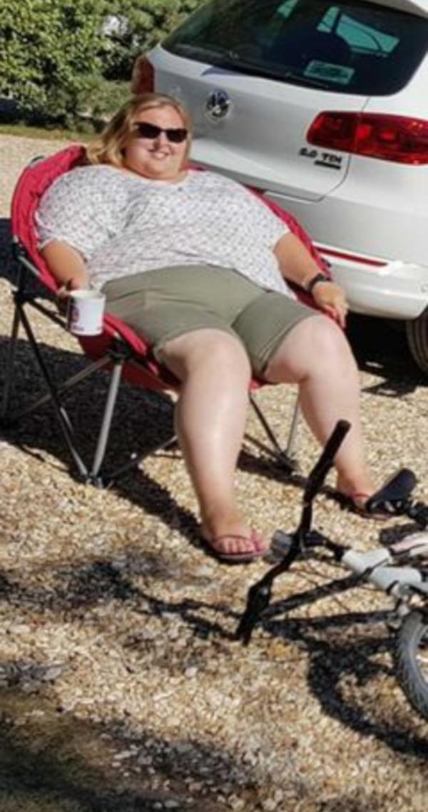 Kelly Ryder stand pe un scaun pliabil, in fata unei masini