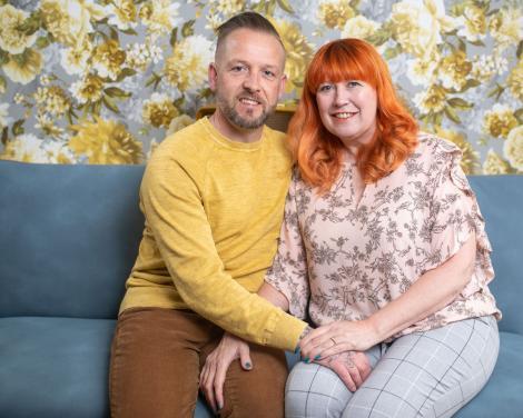 Claire Burke și David, tinandu-se in brate pe o canapea