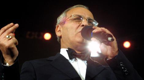 Nelu Ploieșteanu, cântând la microfon, într-un sacou negru