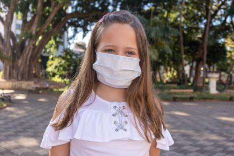Fetiță purtând o mască dprotecție și o bluză albe