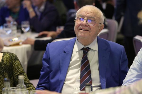 Alexandru Arșinel, într-un costum albastru, cămașă alba și cravată maro