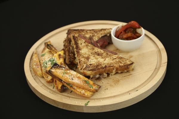 Sandvici cu vită, așezat pe un suport din lemn, alături de sos și cartofi dulci.