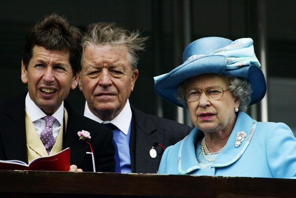 Regina Elisabeta, într-un costum albastru, alături de Sir Michael Oswald, într-un sacou negru