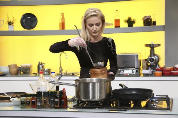 Elwira Petre în platoul Chefi la cuțite, gătește într-o ținută neagră