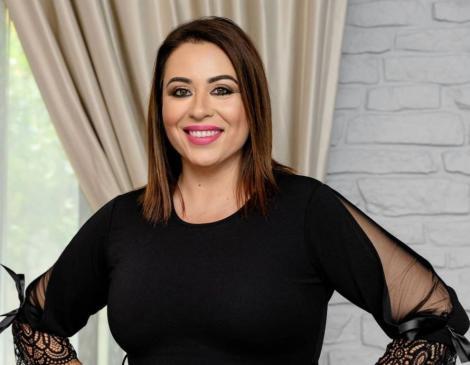 Oana Roman, într-o bluză neagră și zâmbește