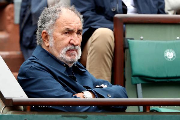 Ion Țiriac, într-un sacou albastru, privind spre terneul de tenis