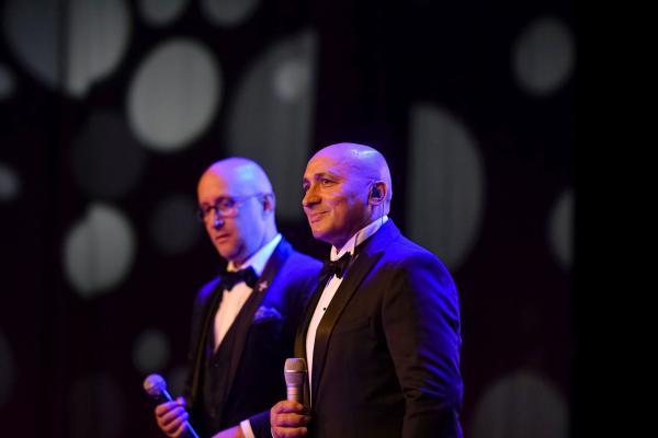 Marcel Pavel în costum negru și cămașă albă, cântă pe scenă