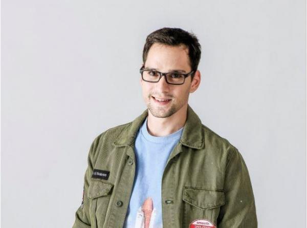 Vlad Gherman cu ochelari, într-un tricou albastru și o bluză verde