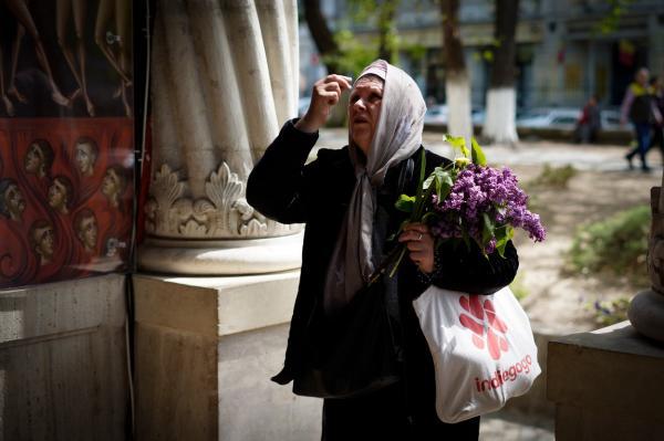 femeie cu flori in brate care se inchina