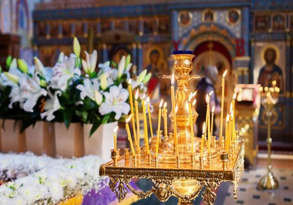 lumanari asezate pe o masa in biserica