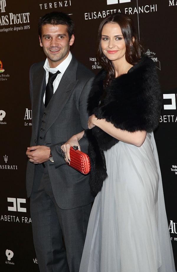 Adelina Chivu într-o rochie lungă și gri, iar Cristi Chivu în costum gri