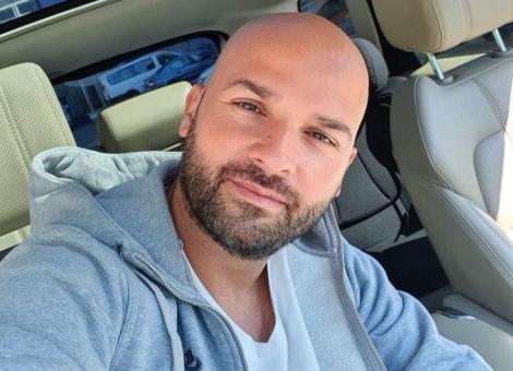 Andrei Ștefănescu într-o bluză gri și tricou alb, stă în mașină și nu are păr