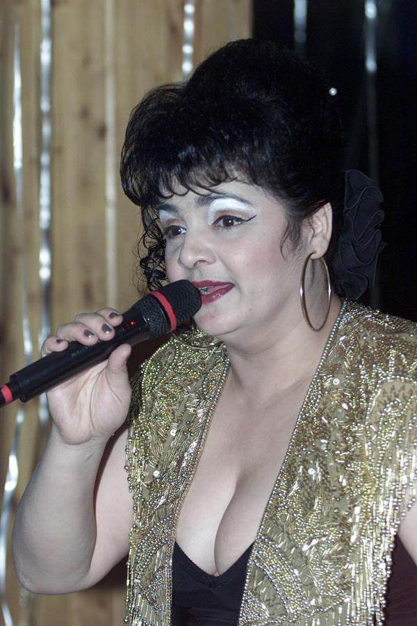 Cornelia Catanga, cântând la microfon, într-o ținutî aurie