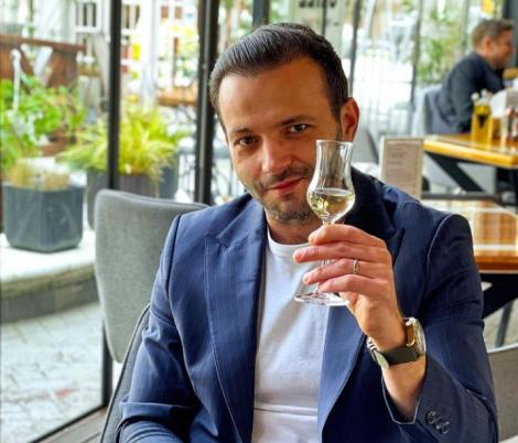 Mihai Morar într-un costum albastru și tricou alb, ține în mână un pahar mic