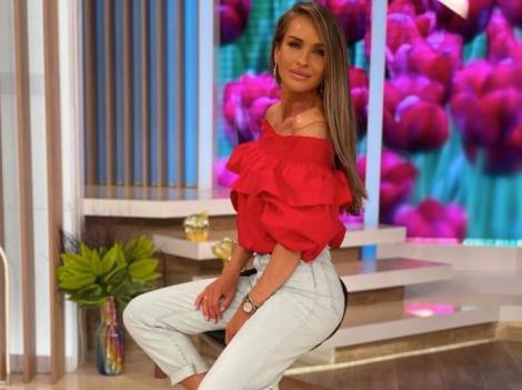 Diana Munteanu într-o bluză roșie și blugi albi