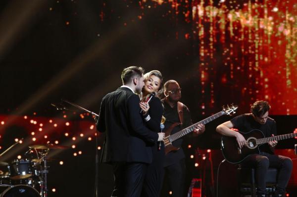 Loredana Groza într-o rochie neagră, decoltată, alături de Adrian Petrache în costum, pe scena X Factor 2020