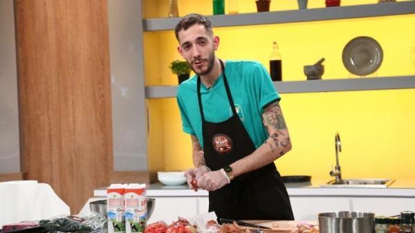 Luca Pintea, îmbrăcat în tricou verde și șorț negru, cu emblema Chefi la cuțite, privește la camera de filmat