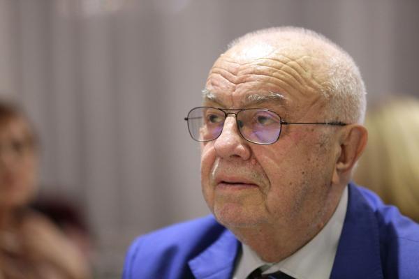 Alexandru Arșinel, într-un sacou albastru și cămașă albă