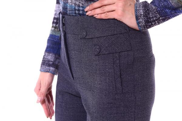 Femeie îmbrăcată în pantaloni, cu mâna în șold și detaliu buzunar închis