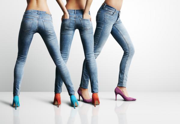 Picioarele a trei femei, îmbrăcate în blugi albaștri, încălțate cu pantofi cu toc și cu mâinile în buzunare