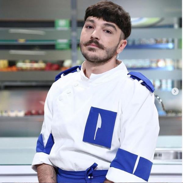 Theo Costache, îmbrăcat în tunică alb albastră, privește spre camera foto