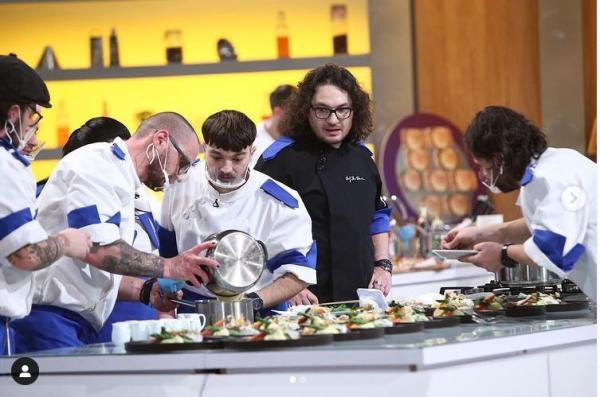 Theo Costache, îmbrăcat în tunică alb albastră, gătește alături de un alt coleg de echipă. În spatele lor este Chef Florin Dumitrescu, care urmărește ce fac cei doi