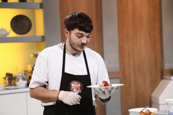 Theo Costache, cu șorțul Chefi la cuțite, este la masa de gătit și ține o farfurie într-o mână