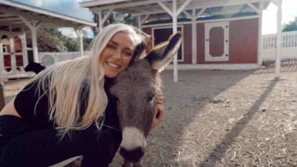 Sarah Lea, pozandu-se cu un magar, la o ferma