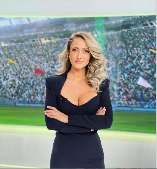 Iuliana Pepene, îmbrăcată într-o rochie neagră, cu decolteu adânc, privește la camera foto