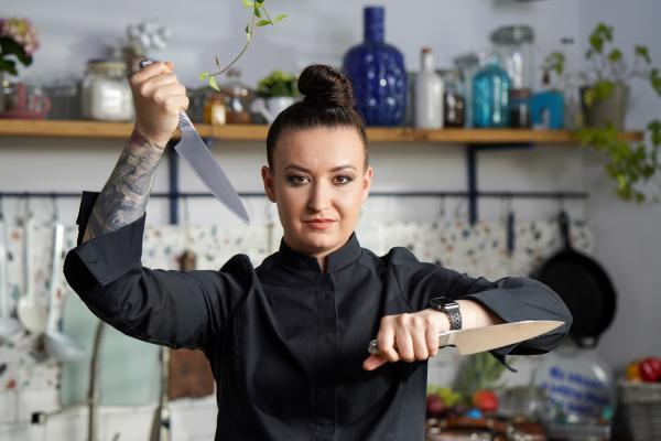 Roxana Blenche în tunică neagră, cu două cuțite în mână