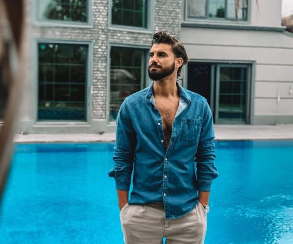 Andi Contantin, într-o cămașă albastră, stă lângă piscină